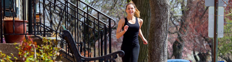 Mujer corriendo por la acera