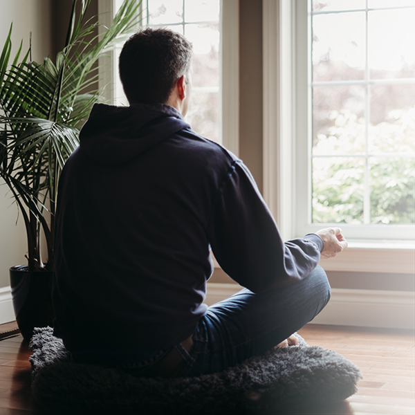 Man meditating by the window