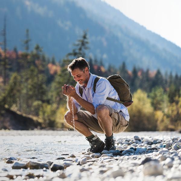 Hombre al lado de un arroyo